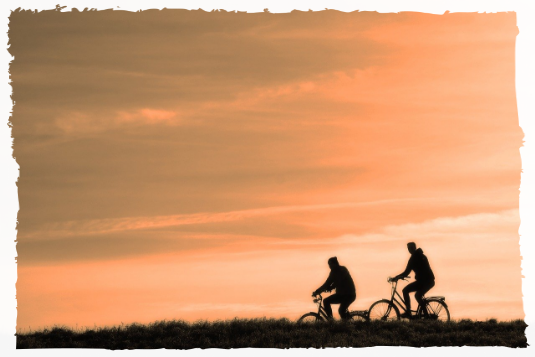 Two people cycling at sunset